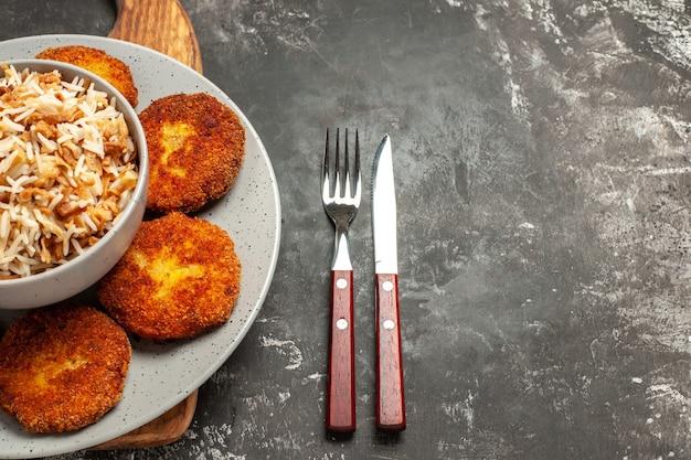 Vista superior de chuletas fritas con arroz cocido en un plato de escritorio oscuro rissole de carne
