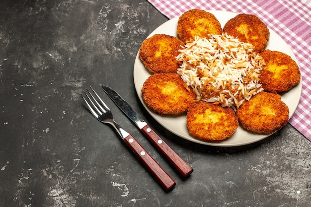 Vista superior chuletas fritas con arroz cocido en rissole de plato de carne de escritorio oscuro