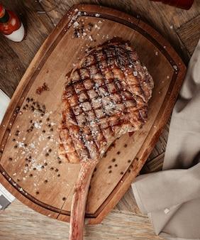 Vista superior de chuletón servido sobre tabla de madera