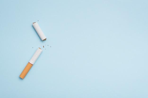 Vista superior del cigarrillo roto sobre fondo azul