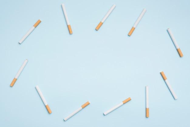 Vista superior de los cigarrillos dispuestos sobre fondo azul