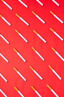 Vista superior de cigarrillos sobre fondo rojo.