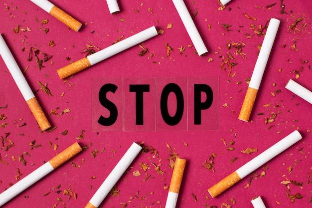 Vista superior de cigarrillos sobre fondo rosa