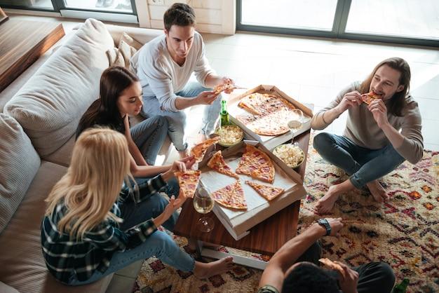 Vista superior de cinco amigos comiendo pizza en casa