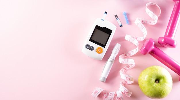Vista superior de cinta métrica, mancuerna, prueba de diabetes y manzana verde