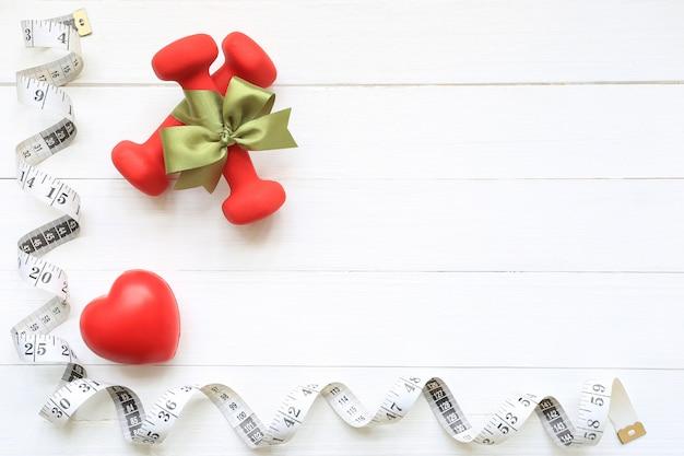 Vista superior de la cinta verde con mancuernas y cinta métrica de corazón sano sobre fondo blanco de madera con copyspace, concepto de cuidado de la salud