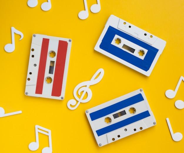 Vista superior de cintas de cassette multicolores con notas musicales decorativas alrededor