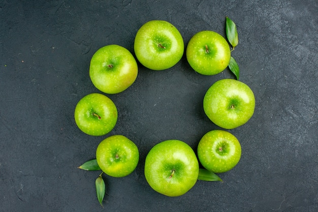 Vista superior círculo fila manzanas verdes en mesa oscura