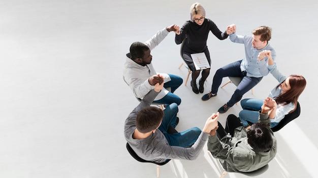 Vista superior del círculo de personas levantando las manos