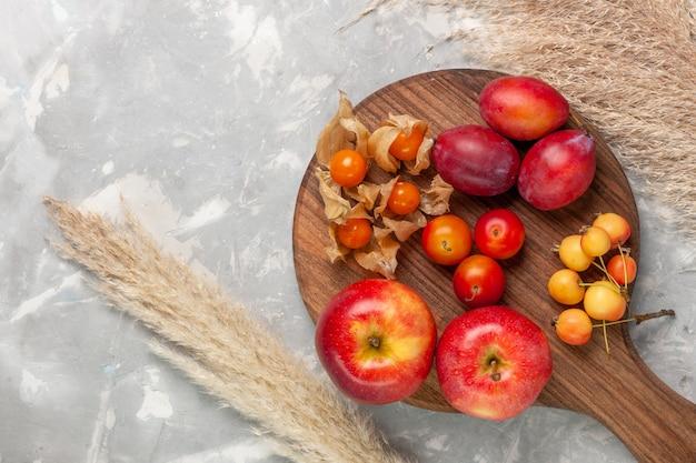 Vista superior ciruelas formadas diferentes frutas agrias y frescas con manzanas en el escritorio blanco claro.