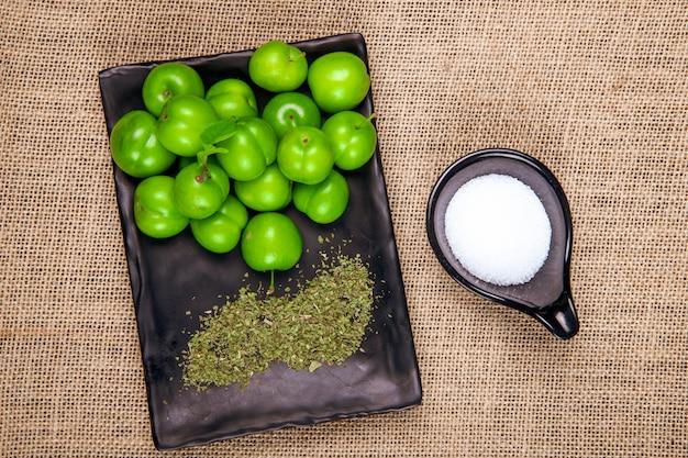 Vista superior de ciruelas verdes agrias con menta seca en una bandeja negra y sal en la mesa de textura de tela de saco