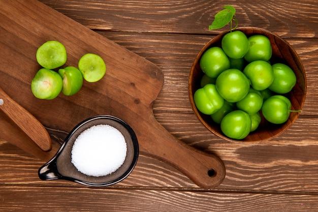 Vista superior de ciruelas verdes agrias en un tazón de madera y ciruelas en rodajas con cuchillo de cocina y sal en un plato en la mesa rústica