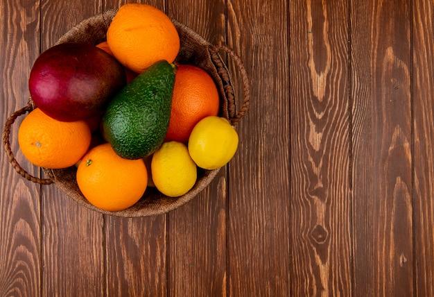 Vista superior de cítricos como mango naranja aguacate limón en canasta en el lado izquierdo y fondo de madera con espacio de copia
