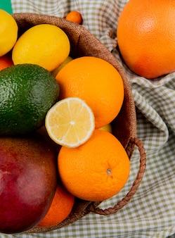 Vista superior de cítricos como mango naranja aguacate limón en canasta sobre fondo de tela escocesa