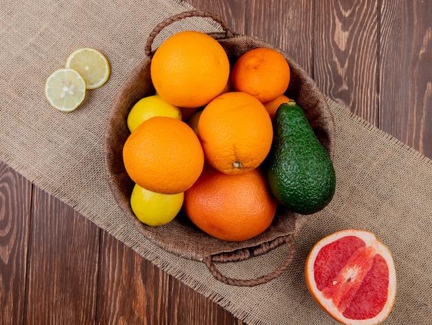 Vista superior de cítricos como naranja aguacate limón en canasta con pomelo sobre tela de saco y fondo de madera