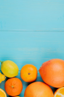 Vista superior de cítricos como naranja limón y mandarina sobre fondo azul con espacio de copia