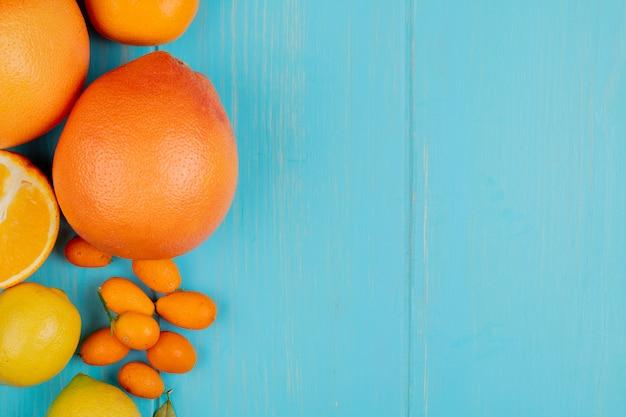 Vista superior de cítricos como naranja mandarina limón y kumquats en el lado izquierdo y fondo azul con espacio de copia