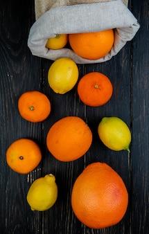 Vista superior de cítricos como pomelo limón mandarina derramando saco sobre fondo de madera