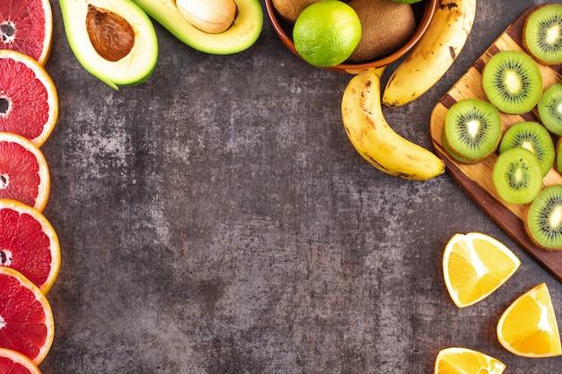 Vista superior de cítricos pomelo aguacate kiwi naranja fruta y plátanos con espacio de copia