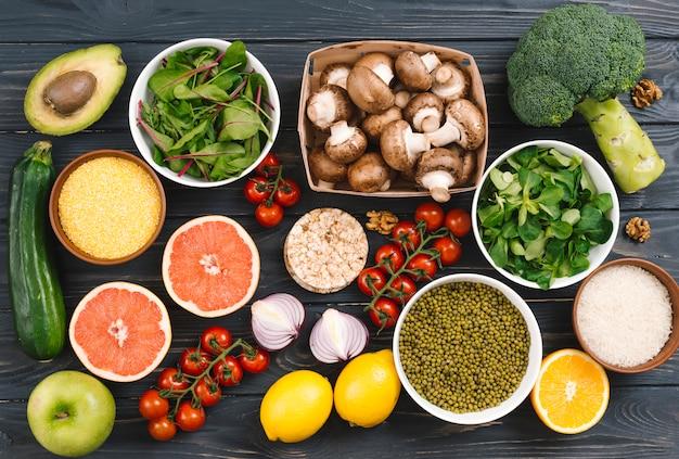 Vista superior de los cítricos; verduras y legumbres en mesa negra.