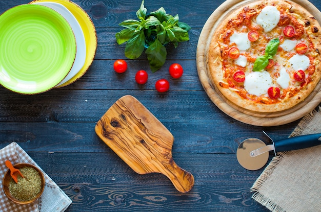 Vista superior de la clásica pizza italiana margarita sobre una mesa de madera con coberturas