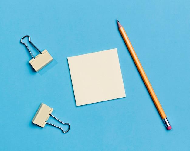 Vista superior de clips de papel y lápiz sobre el escritorio