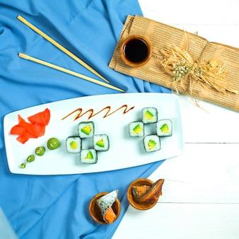 Vista superior de la cocina tradicional japonesa rollo de sushi negro con arroz aguacate y queso crema servido con salsa de soja, jengibre y wasabi en azul y blanco