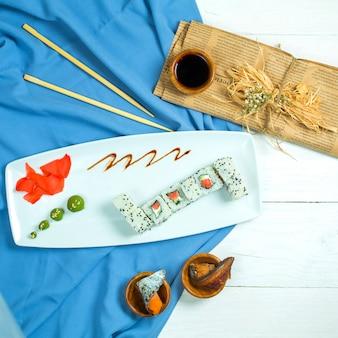 Vista superior de la cocina tradicional japonesa sushi roll con aguacate de salmón y queso crema en azul y blanco