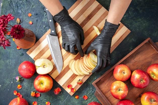Vista superior cocinera cortando manzanas en la superficie gris