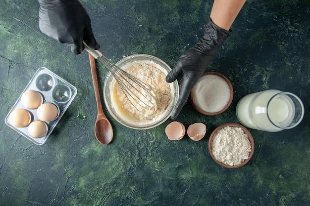 Vista superior cocinera mezclando harina en un plato con huevos sobre una superficie oscura