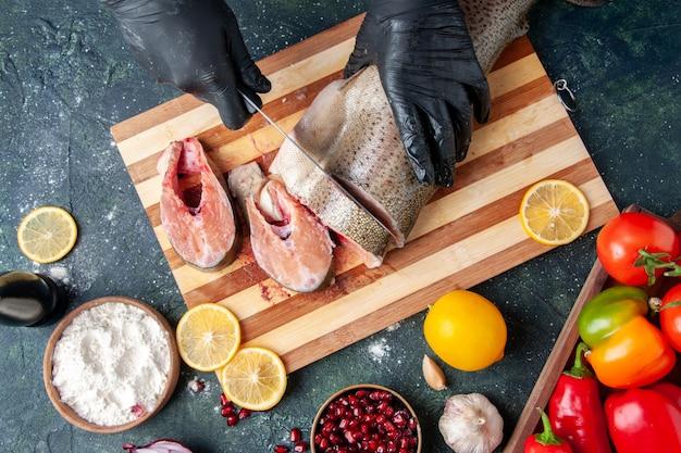 Vista superior del cocinero cortando pescado crudo en la tabla de cortar, tazón de harina, semillas de granada en la mesa