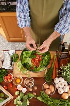 Vista superior del cocinero irreconocible que agrega perejil a la ensaladera
