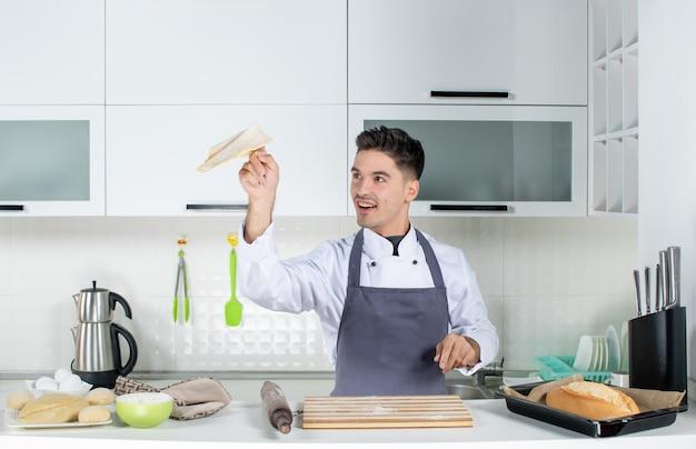 Vista superior del cocinero joven sonriente en uniforme de pie detrás de la mesa en la cocina blanca