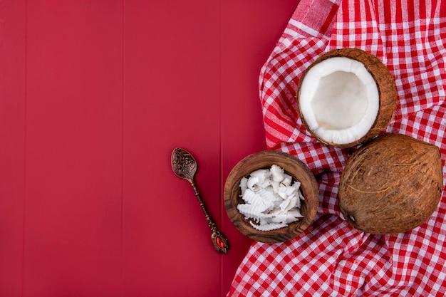 Vista superior de cocos marrones con pulpas de coco en un cuenco de madera con cuchara sobre mantel a cuadros rojo y blanco sobre rojo con espacio de copia