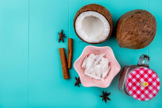 Vista superior de cocos marrones con pulpas de coco en un tazón rosa con jugo de canela en frasco de vidrio en azul