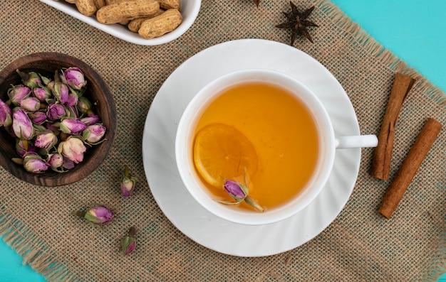 Vista superior de cogollos secos con una taza de té y canela sobre una servilleta de color beige