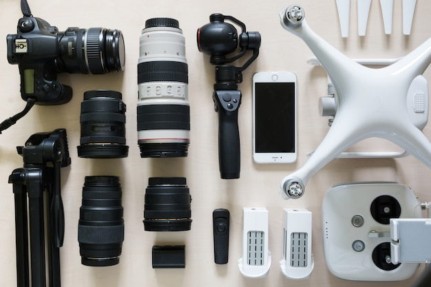 Vista superior de la colección de equipos fotográficos con cámara, videocámara, lente y dron