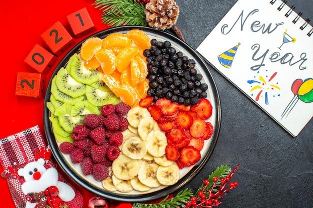 Vista superior de la colección de frutas frescas en accesorios de decoración de plato de cena ramas de abeto y números calcetín de navidad en una servilleta roja próximo cuaderno con dibujos de año nuevo sobre fondo negro