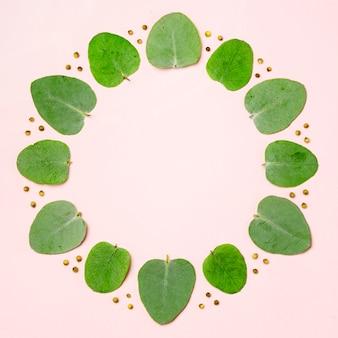 Vista superior colección de hojas verdes sobre fondo rosa