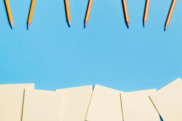 Vista superior colección de lápices y notas adhesivas