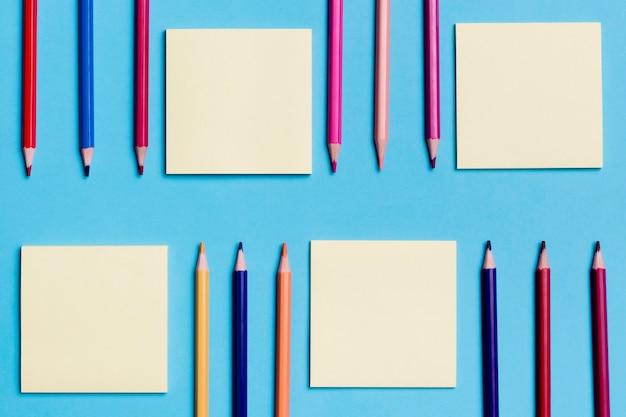Vista superior colección de notas adhesivas y lápices.