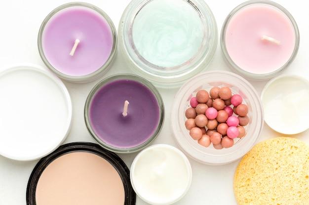 Vista superior colección de productos cosméticos y velas.