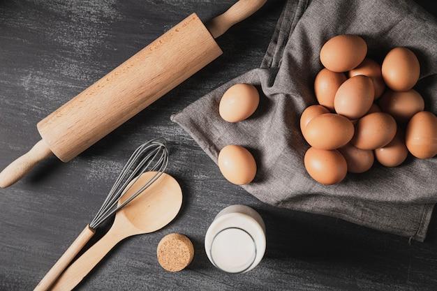 Vista superior colección de utensilios de cocina junto a huevos