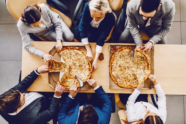 Vista superior de colegas hambrientos sentados a la mesa y comer pizza para el almuerzo. interior de la firma corporativa.