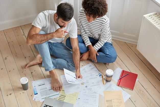 Vista superior de los colegas de la mujer y el hombre tienen una conversación sobre proyectos comunes, documentos de estudio