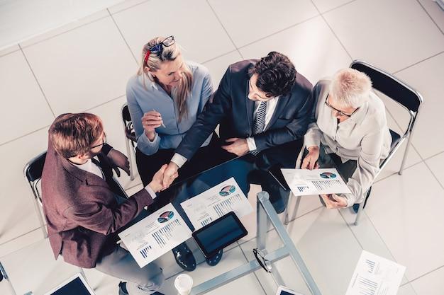 Vista superior. colegas de negocios dándose la mano de acuerdo. concepto de negocio.