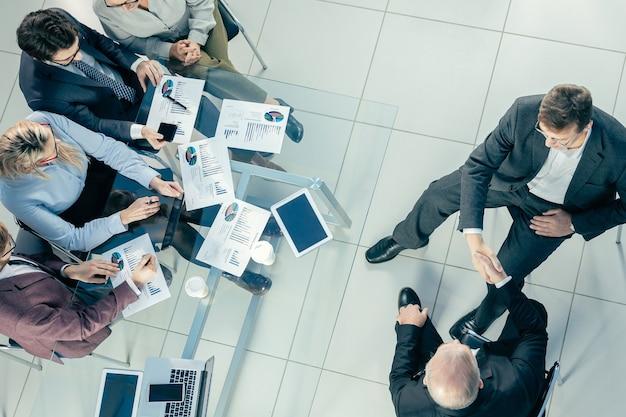 Vista superior de colegas de negocios dándose la mano unos a otros