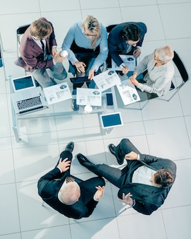 Vista superior de colegas de negocios discutiendo datos financieros en una reunión de oficina