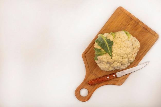 Vista superior de coliflor fresca en una tabla de cocina de madera con cuchillo en una pared blanca con espacio de copia