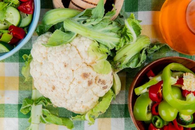 Vista superior de coliflor con pimientos en rodajas y ensalada de verduras con mantequilla derretida sobre tela escocesa
